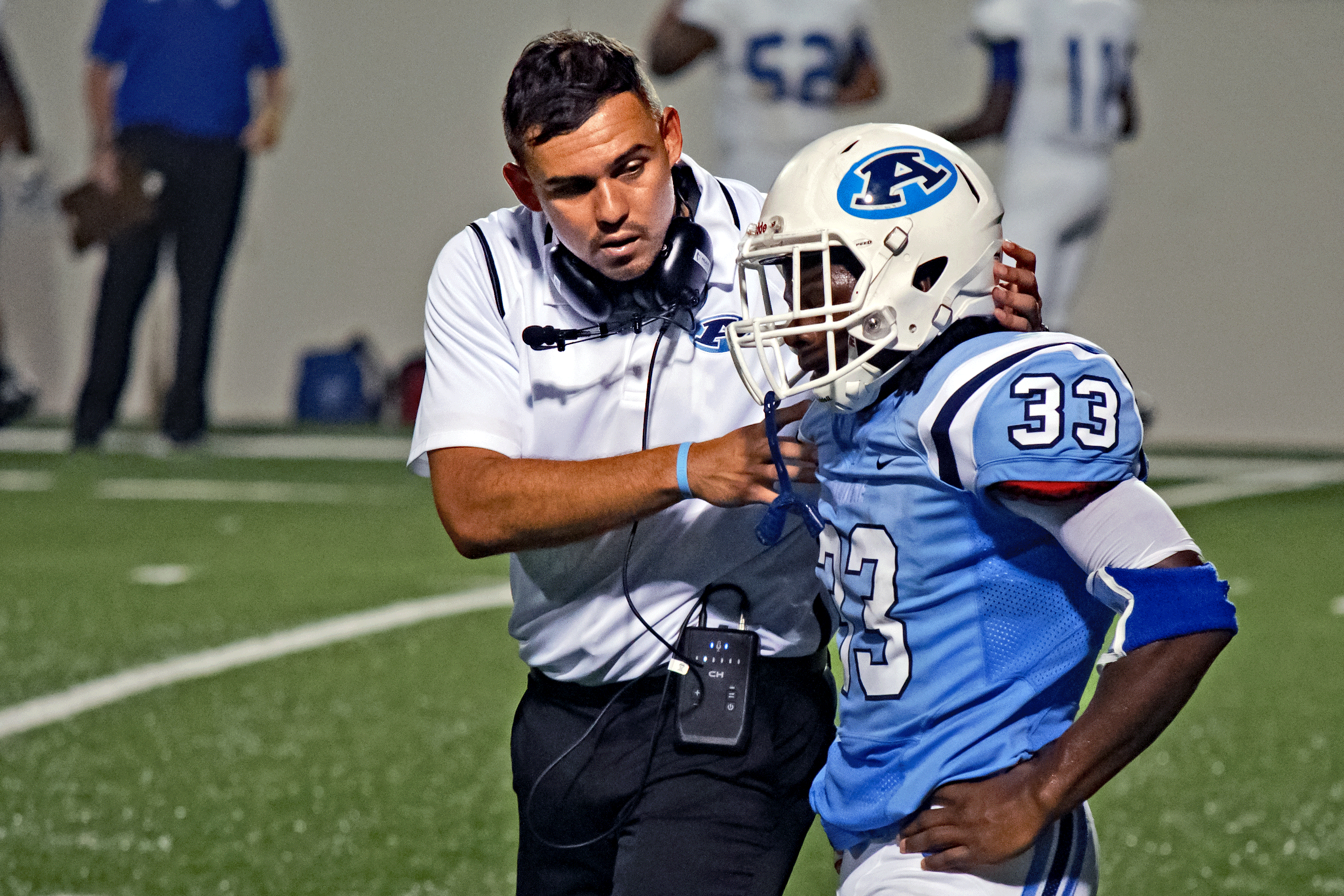 Aldine head coach James Kowalewski gives pointers to Mustang RB Michael McLennon during the 2016 season.